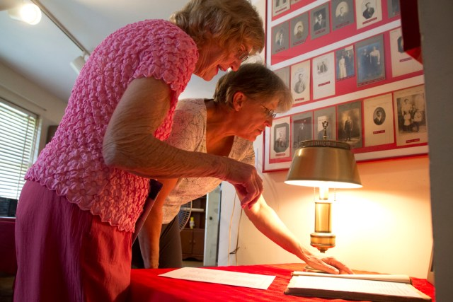 Volunteers Irene Pendzick (left) and Maria Tobiasz look over a list of Polish Town immigrants at the recreated exhibit Monday afternoon. (Credit: Paul Squire)