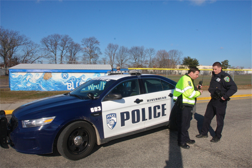 Riverhead police officer Doug Geraci (left) arrived on the scene at Riverhead High School Thursday. (Credit: Barbaraellen Koch)