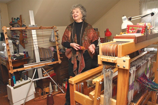 Natural fibers artist Barbara Ringewald of Cutchogue, wearing a shawl she made, demonstrates how she sets up the loom in her home studio before starting work on a new piece. (Credit: Barbaraellen Koch)