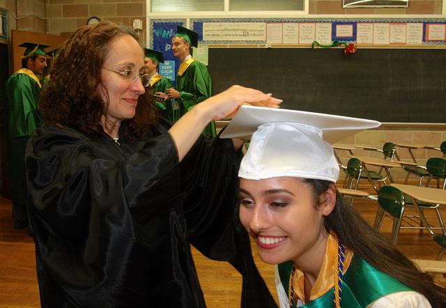 Juliet Fusco of Riverhead bends down a little to have teacher Monique Hernandez add her tassel. (Credit: Barbaraellen Koch)