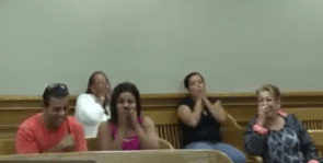 Other citizens waiting to have their cases heard in the courtroom react to Jacob's response to Judge Caprio.
