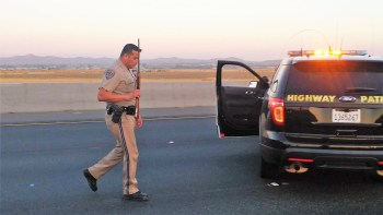 A CHP officer recovers one of two rifles the suspect had on the freeway. William Hayes photo