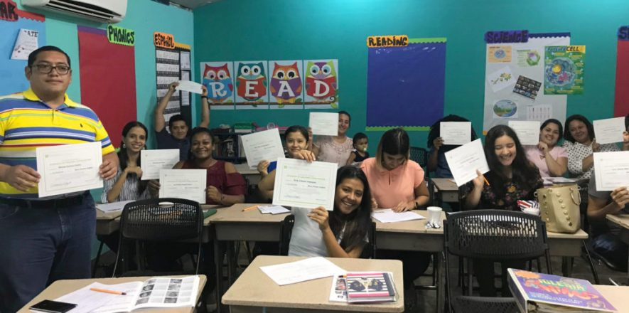 A classroom of Hondurans holding up their Darkness 2 Light certificates