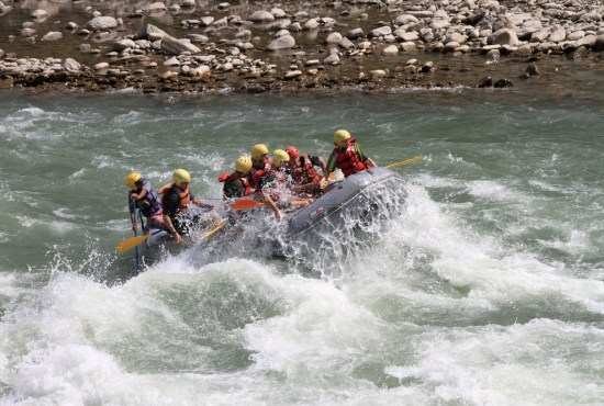 rafting tips for beginners: raft traversing difficult whitewater with people balancing on raft