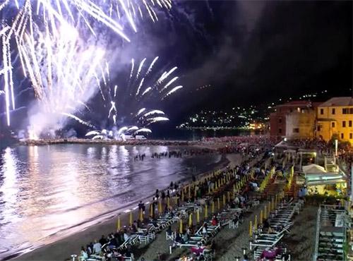 Fuochi d'artificio sul mare visti dalla spiaggia attrezzata