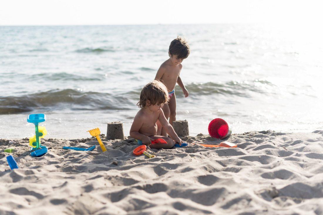 Mar ligure in primavera con bambini che giocano sulla spiaggia