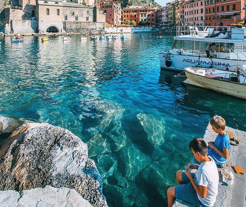 Mare in Liguria bambini che danno da mangiare ai pesci