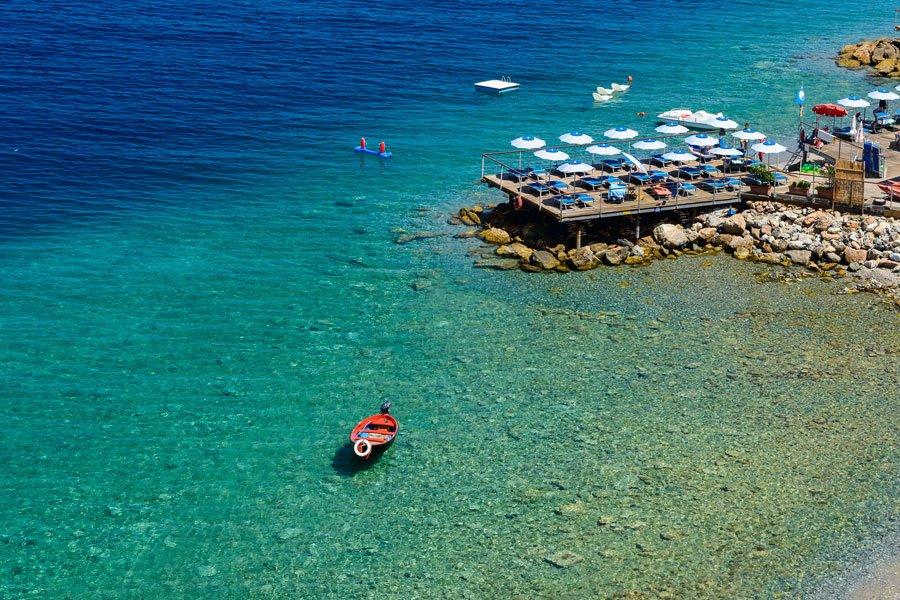 Noli spiaggia con barca e acqua trasparente
