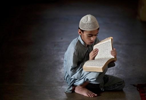 A muslim boy reading Quran from the Mushaf