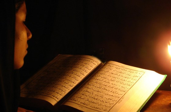 A man reading Quran in darkness with a deep concentration