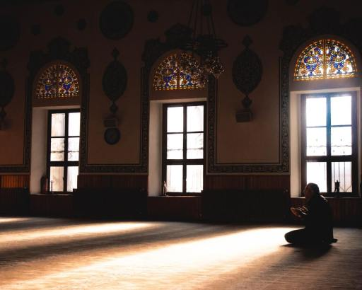 A muslim sitting alone at the mosque and praying Allah