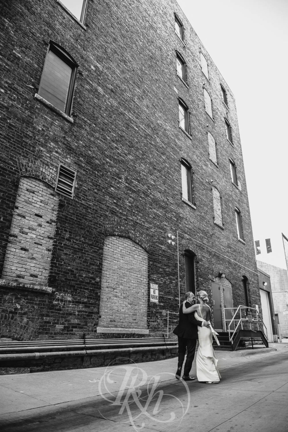 Bride and groom dancing in alley