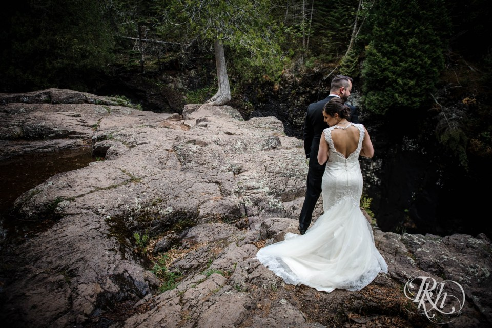 Bride and groom standing on cliff