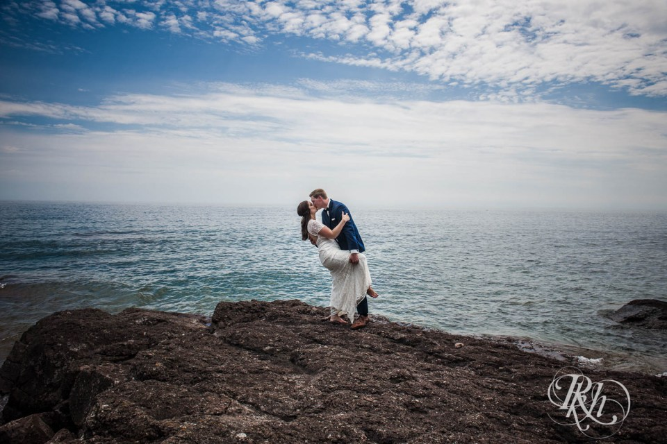 Bride and groom dip and kiss on Lake Superior