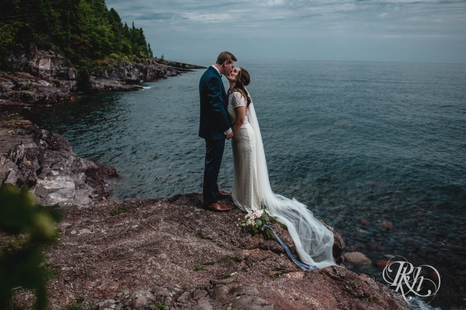 Bride and groom kiss on cliff