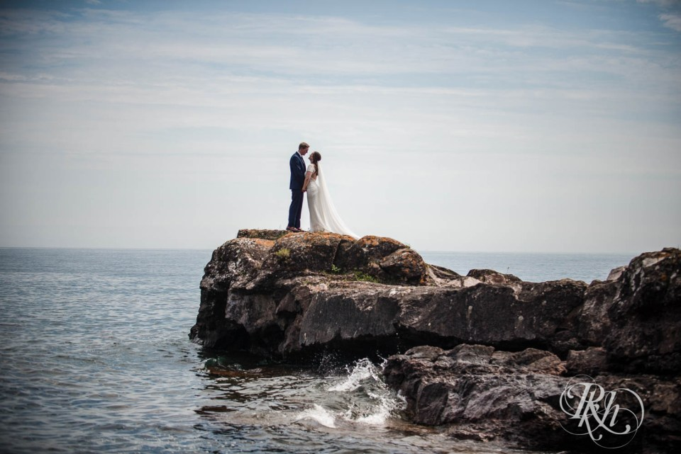 Bride and groom on cliff on Lake Superior