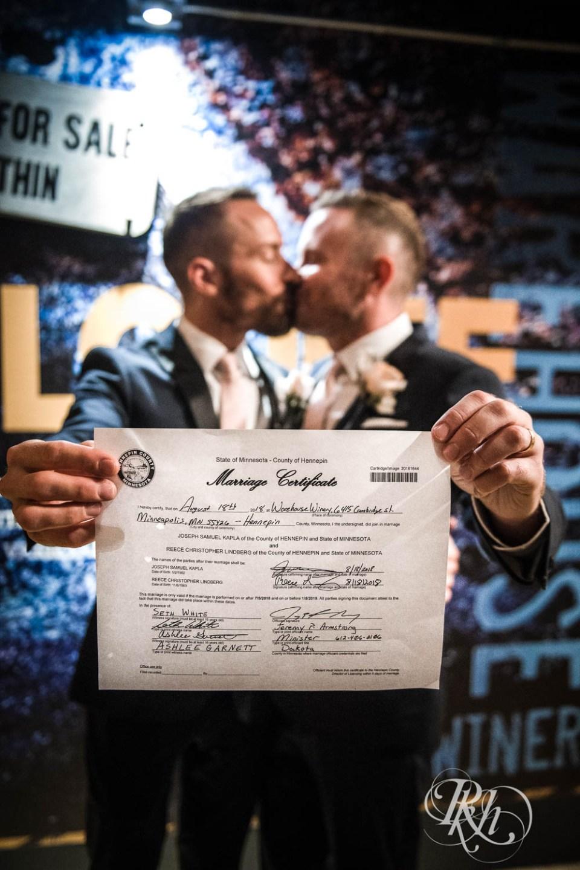 Grooms holding wedding certificate