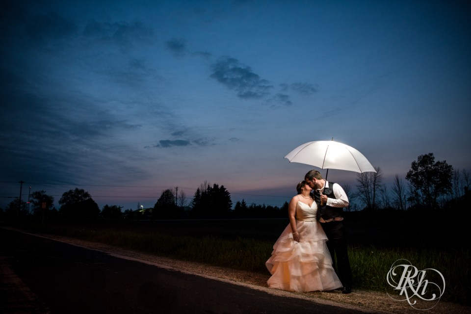 Bride and groom under umbrella night