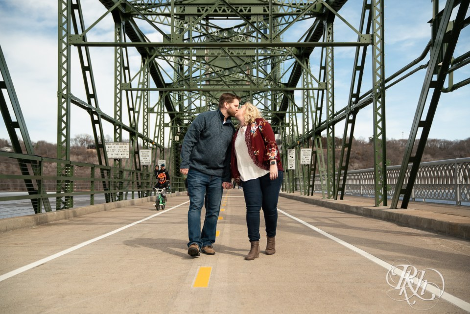 sunny engagement photography stillwater minnesota bridge kiss walking