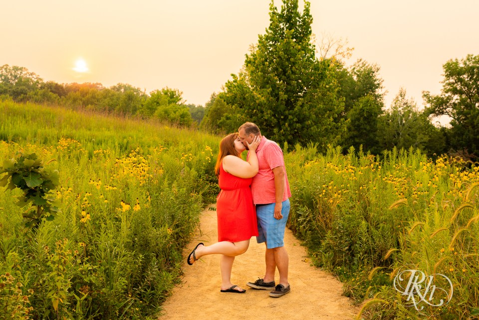 summer engagement photography couple kissing in flower field