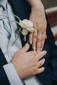 newlyweds showing wedding rings on ring fingers