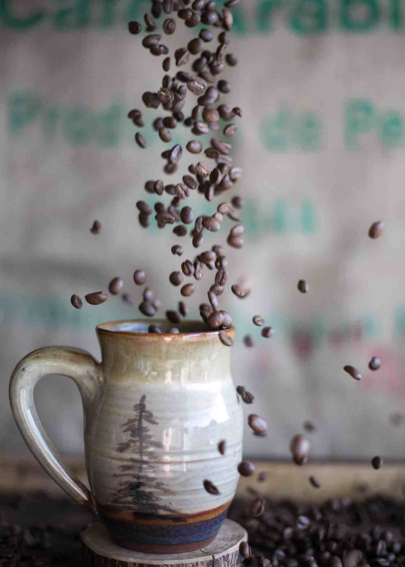 Coffee beans falling into coffee cup