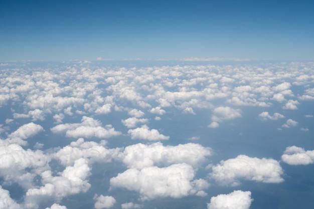 vista-cielo-azul-sobre-blanco-mayormente-nublado-ventana-avion_7186-2167