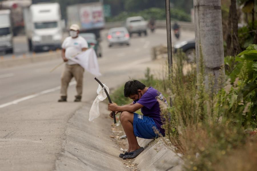 Un niño ondea una bandera blanca en la carretera pidiendo ayuda por hambre debido a la crisis economica provocada por el coronavirus, el 29 de abril de 2020 en El Tejar (Guatemala). EFE/Esteban Biba