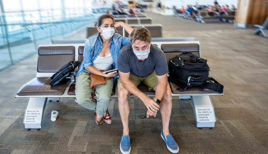 1140-travelers-with-masks-at-airport-esp.imgcache.rev.web.900.518