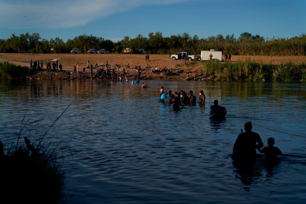 Fotografía del pasado miércoles de migrantes, en su mayoría haitianos, cruzando el Río Bravo en la frontera entre México y EE.UU. EFE/EPA/ALLISON DINNER