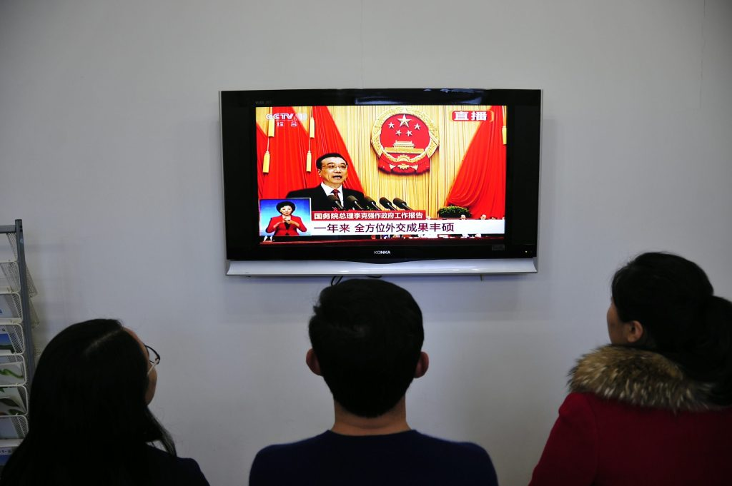 Chinese people watch live television coverage at a conference room in Yantai, east China's Shandong province as Chinese Premier Li Keqiang delivers his report during the opening ceremony of the National People's Congress in the Great Hall of the People in Beijing on March 5, 2016. Chinas Communist-controlled parliament opened its annual session on March 5 and is expected to approve a new five-year plan to tackle slowing growth in the worlds second-largest economy.  / AFP / STR / China OUT        (Photo credit should read STR/AFP/Getty Images)