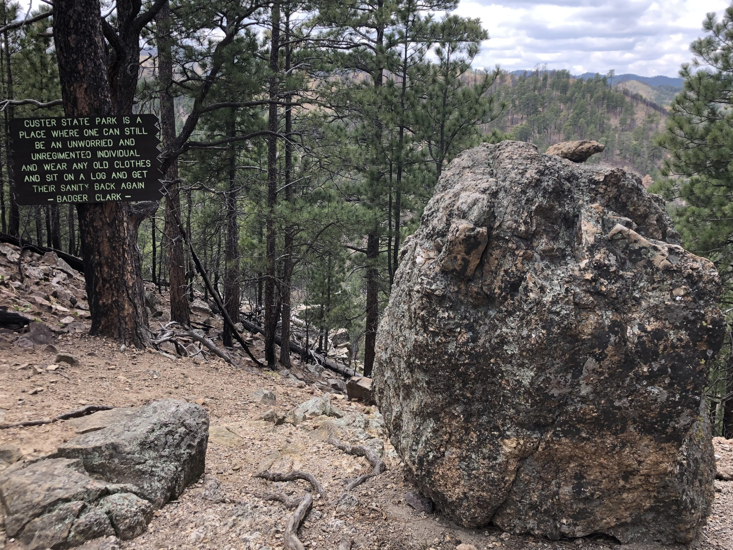 A sign inviting hikers to sit and rest near a giant boulder