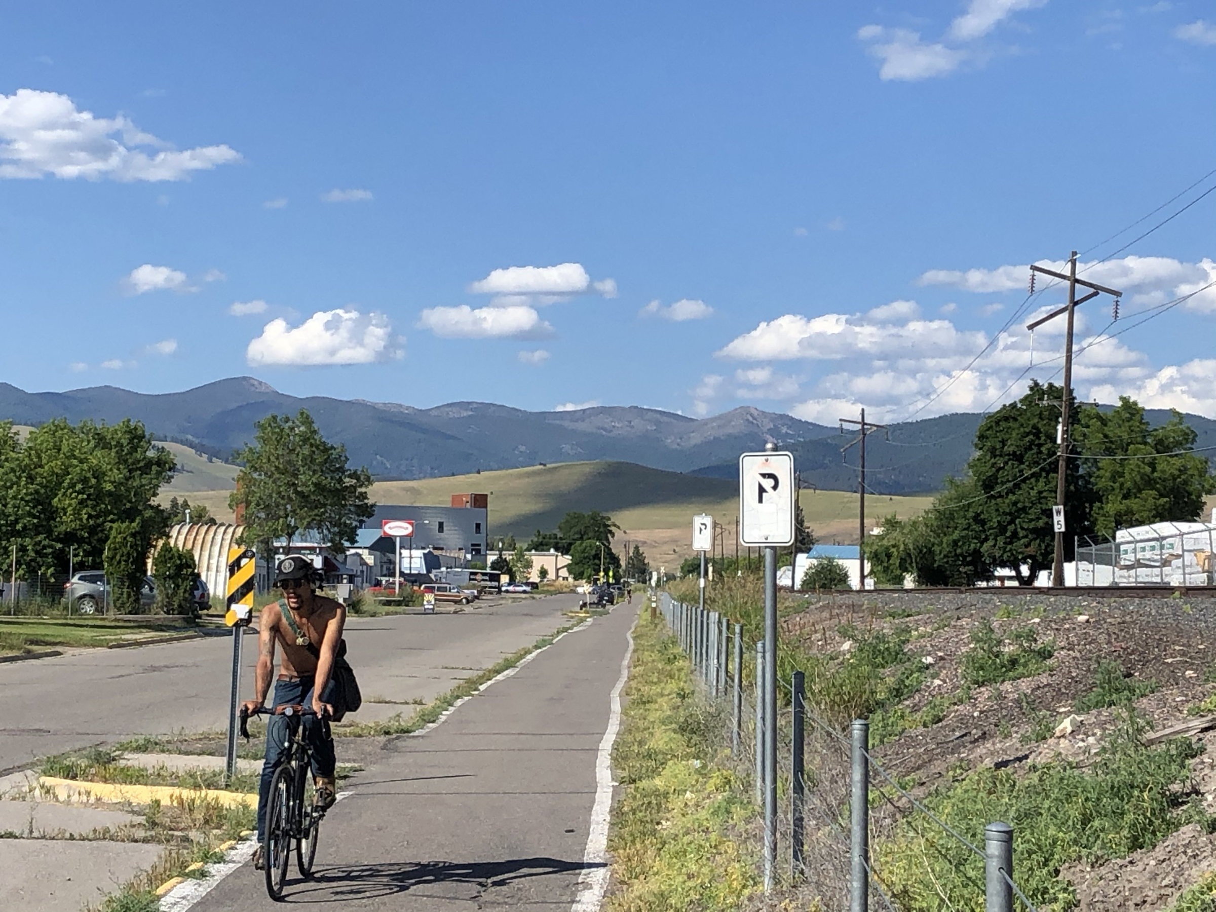 Riding a bike path through the city of Missoula with mountains in the background