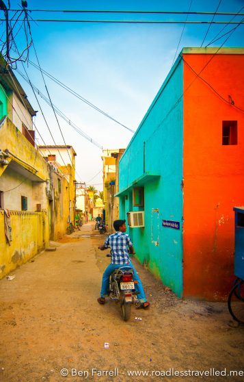 A local boy stops his scooter in a colourful lane way to take another look at some pretty passing girls.