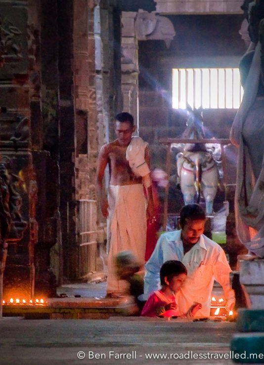 A father helps his son light a candle for offering in an ancient temple. Kanchipuram, Tamil Nadu, India.