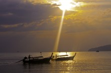 A shard of sunlight breaks through the clouds amongst traditional Thai fishing boats. Krabi, Thailand.