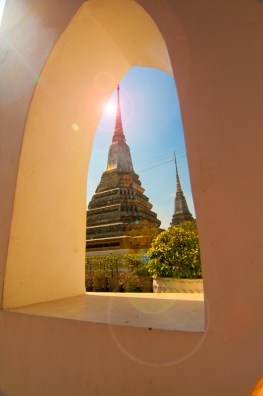 A golden temple reflects the sun through the window of a neighbouring temple. Bangkok, Thailand.