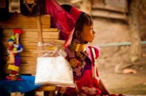 A young girl plays around her mothers market stall. Chiang Mai, Thailand.