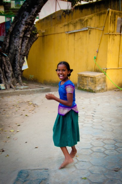 A happy young girl, living in the moment in one of India's slums.