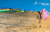 A beach vendor wanders along Marina Beach ringing his bell selling birght fairy floss to beach goers and fisherman. Chennai, India.