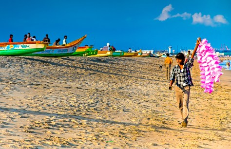 A beach vendor wanders along Marina Beach ringing his bell selling birght fairy floss to beach goers and fisherman. Chennai, India.