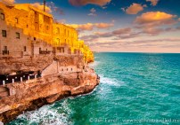 The medieval fishing village of Polignano a Mare. Perched high up on the cliff face it's arched windows stare out at the bright blue Adriatic Sea.
