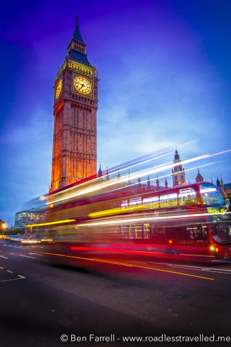 An iconic double-decker red bus passes by Big Ben in London, UK.