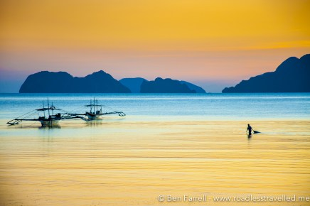 A fisherman drags in his nets as the sun sets off Coron Coron beach, Philippines.