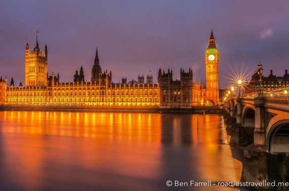 The houses of parliament reflect of the cold river Thames in London, UK.