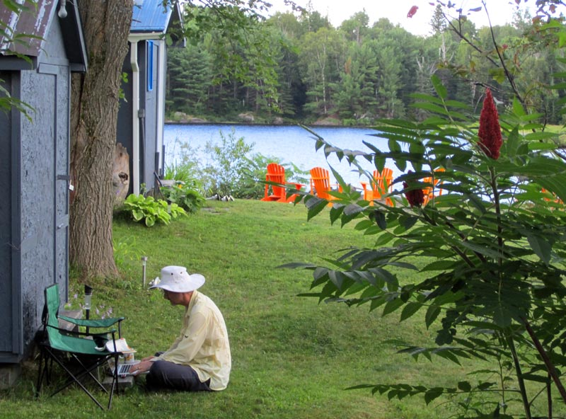 Glenn Cameron sitting on the grass at a summer cottage