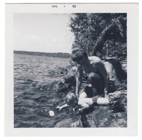 infant reaching into West Hawk Lake, 1962