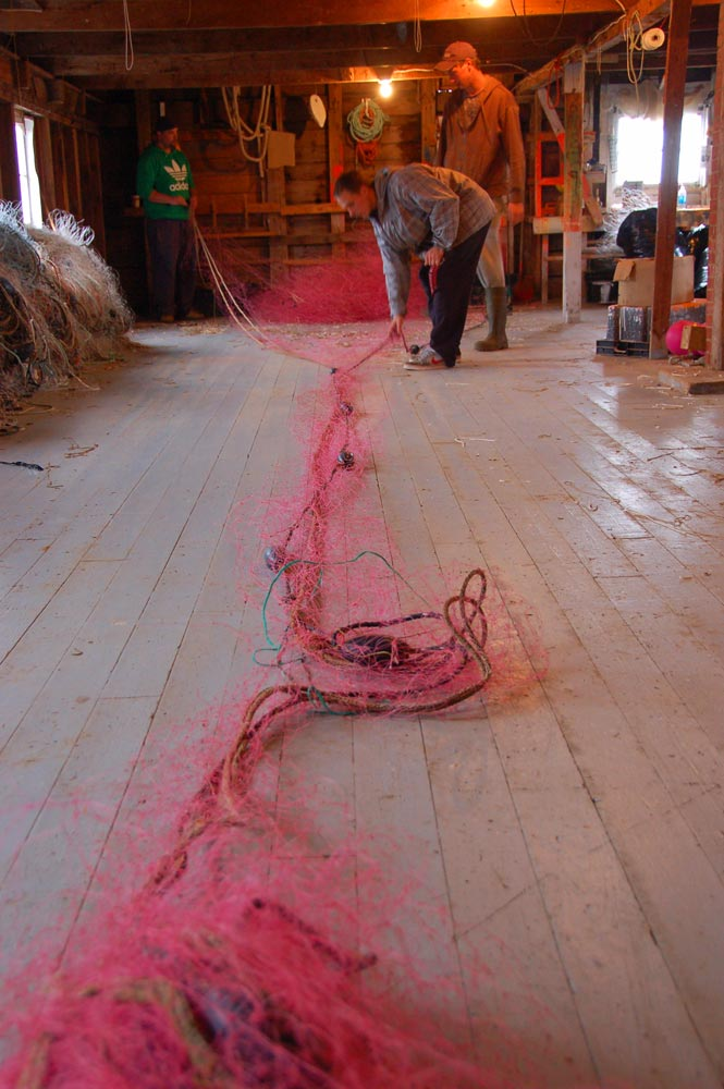 Mending fishing nets in a shed at Seal Cove on Grand Manan Island, New Brunswick, Canada