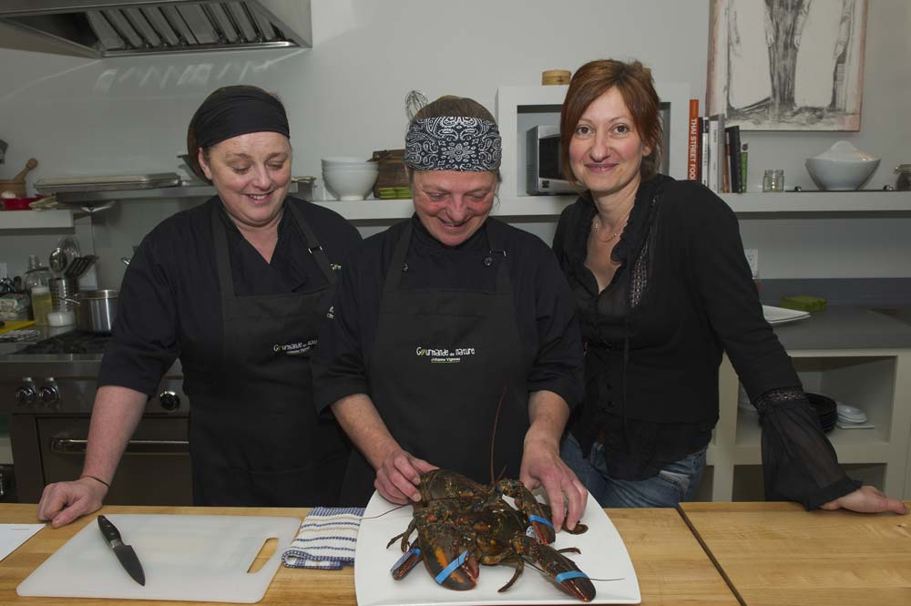 Three ladies prepare lobster on the Îles de la Madeleine