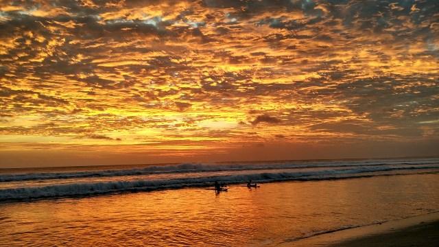 Bali surfers at sunset